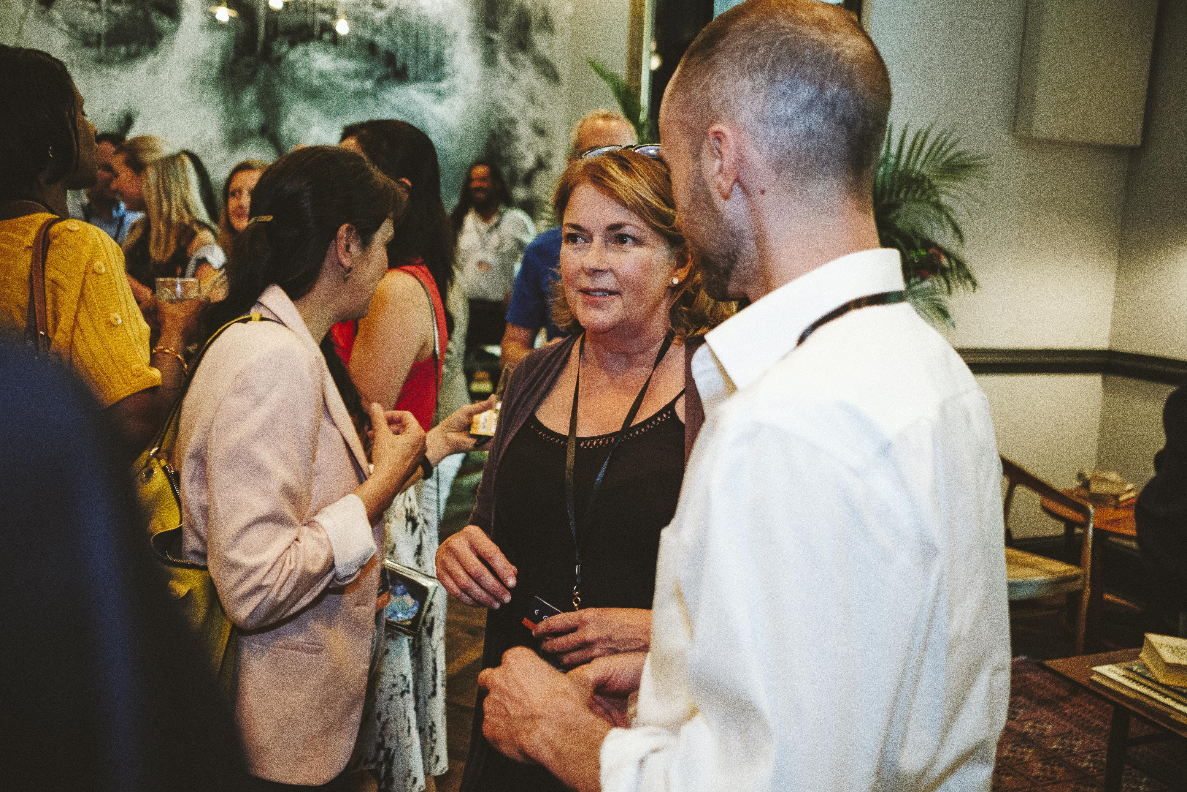 A male and female chatting at a networking event at the Common House in Charlottesville.